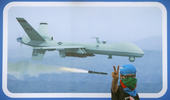 Un partidario del partido islamista Jamaat-e-Islami muestra el signo de la victoria frente a una imagen de un avión no tripulado, durante una manifestación contra los ataques de estos aviones en Karachi, Pakistán, el pasado 04 de junio. Un avión no tripulado de EE.UU. mató al ciudadano norteamericano y líder de al-Qaeda figura Anwar al-Awlaki en Yemen en septiembre. (Foto: Athar Hussain / Reuters)