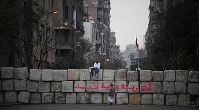 """Día de elecciones en Egipto. En la foto, un manifestante egipcio sentado en una barricada de hormigón en plena Plaza Tahrir de El Cairo, en la que se puede leer en árabe """"La libertad llegará para siempre"""".  (Manu Brabo/AP)"""