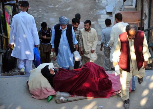 Paquistaníes pasan por delante de una mujer sin hogar que descansa sobre un puente ferroviario en Rawalpindi el 13 de Noviembre.  (Foto: Farooq Naeem / AFP / Getty Images)