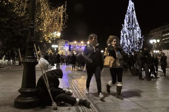 Un hombre pide dinero durante las celebraciones de Navidad y la iluminación de la plaza Syntagma de Atenas el centro de 9 de diciembre. (Foto: Louisa Gouliamaki / AFP / Getty Images)
