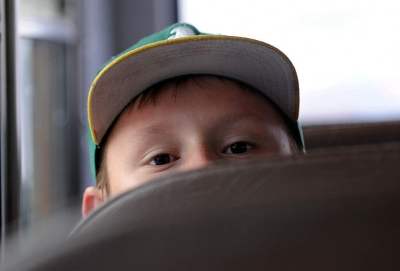 Wiley James Hickman se asoma sobre el asiento de un autobús escolar camino a la escuela en  Reno, Nevada. Este niño no tiene casa. (Foto: Andy Barron / Associated Press / El Reno Gazette-Journal)