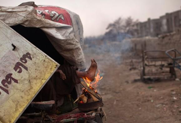 Hombre calienta el pie con las llamas de un incendio en Kabul, Afganistán. (Foto: Ahmad Masood / Reuters)