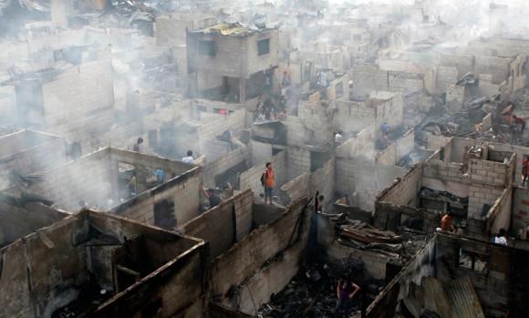 Personas que viven en las ruinas de sus casas después de un incendio en Makati City, en Manila. El incendio arrasó al menos 900 casas precarias dejando a más de 2.000 familias sin hogar, dijo la policía. (Foto: Erik De Castro / Reuters)