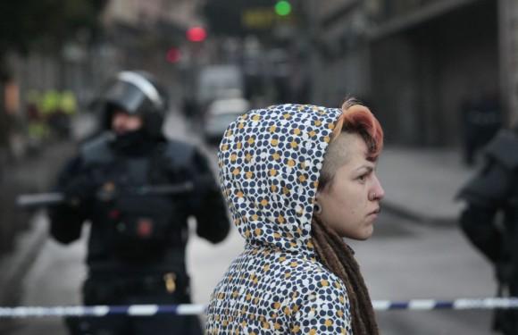 En la imagen, una joven observa el desalojo desde la barrera policial.