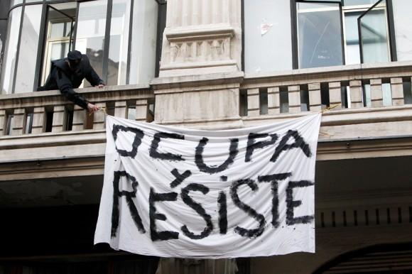 Un policía retira una pancarta de la fachada del hotel Madrid.