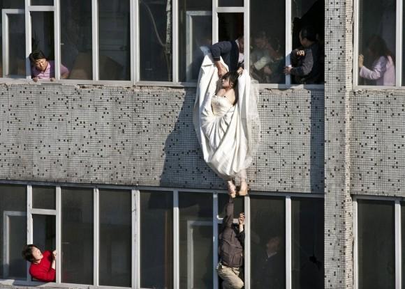 Una novia en dificultades los intentos de suicidio en China  después de su prometido abruptamente canceló su matrimonio. Sin embargo,  en su vestido de novia, ella trató de suicidarse saltando de una  ventana de un edificio de planta séptima. Justo cuando ella saltó, un  hombre logró alcanzar y salvarla.