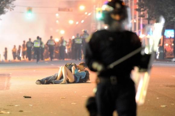 El australiano Scott Jones besa a su novia canadiense Alex Thomas después de haber sido derribado al suelo por el escudo antidisturbios de un policía en Vancouver, Columbia Británica. Los canadienses se amotinaron después de los Canucks de Vancouver perdieron la Copa Stanley de los Bruins de Boston. (Getty Images / Lam enriquecido)
