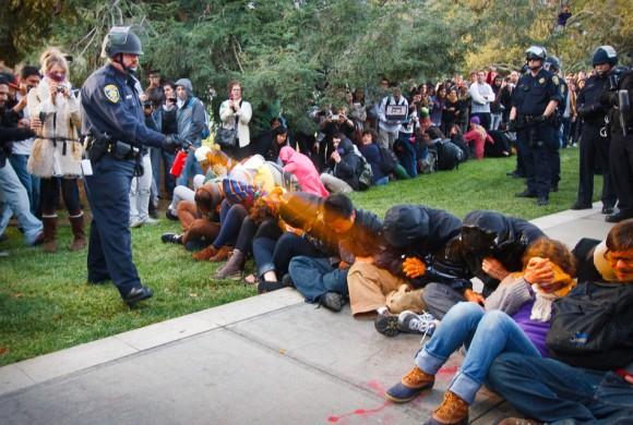 Un policía de Universidad de California en Davis baña a  estudiantes durante una protesta pacífica de