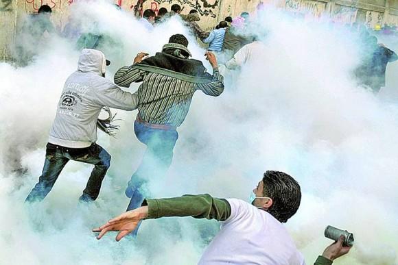 Manifestante devuelve una bomba lacrimógena lanzada originalmente por la policía.