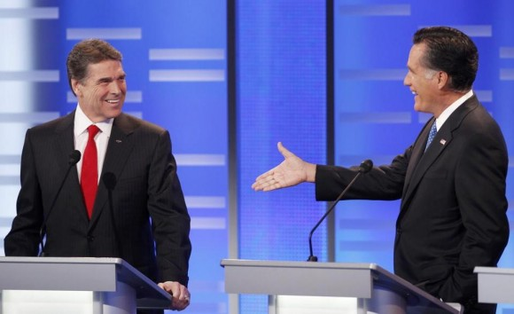El candidato presidencial republicano Mitt Romney extiende su mano a su rival Rick Perry cuando este lo reta a una apuesta de $10.000 durante un debate en Iowa.