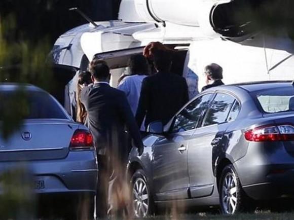 La presidenta argentina, Cristina Fernández (extremo superior al centro) sale de un helicóptero rodeada de personal de seguridad y familiares en las afueras del Hospital Austral en Pilar, afueras de Buenos Aires, ene 4 2012.