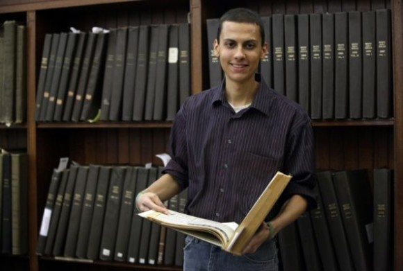 El estudiante Malcolm Burnley, de 22 años, con una copia de la edición de 1961 de El Herald en la Biblioteca de la Universidad de Brown. Foto AP / Stephan Savoia
