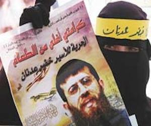Una palestina muestra un cartel con la imagen del preso palestino Jader Adnan, detenido sin cargos desde diciembre pasado por el Ejército israelí, durante una protesta para pedir su liberación, en Hebrón, Cisjordania, hoy, martes, 21 de febrero de 2012. Jader Adnan decidió hoy abandonar su huelga de hambre tras 66 días sin comer en protesta por su arresto sin acusación y por supuestos malos tratos por parte de soldados israelíes. EFE/Abed Al Hashlamoun