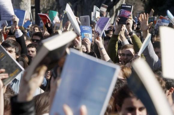 Estudiantes muestran libros durante la concentración frente al  Lluís Vives. Foto: KAI FÖRSTERLING (EFE)