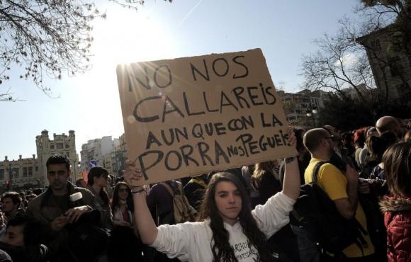 Una joven muestra una pancarta durante la concentración frente al  instituto Lluís Vives de Valencia. JOSE JORDAN (AFP)