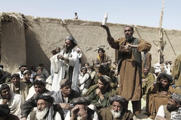 Un poblador afgano, a la derecha, muestra un frasco supuestamente utilizado por las fuerzas de EE.UU. durante la matanza del domingo de la población civil en una ceremonia de oración por las víctimas en Panjwai, provincia de Kandahar, al sur de Kabul, Afganistán, martes, marzo. 13, 2012. (Foto AP / Allauddin Khan