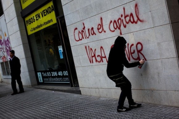 En Barcelona, un manifestante pinta en la pared una de las consignas de la Huelga General.  Foto: Emilio Morenatti / AP.