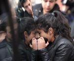 Una joven llora desconsolada junto a un coche fúnebre. Foto: AFP