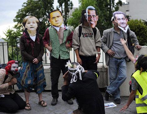 Manifestantes con máscaras de la canciller alemana Angela Merkel, el primer ministro italino, el presidente estadounidense Barack Obama y el presidente francés Nicolas Sarkozy durante la cumbre del G-8 en mayo de 2011. Foto: EFE/Vanguardia