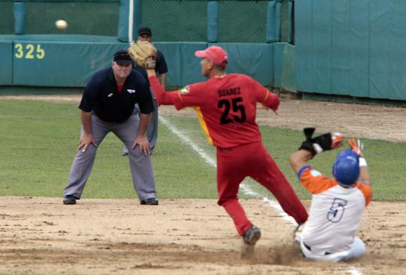 Eriel Sanchez llega antes que la pelota a la primera base, pero es puesto Out.   Foto: Ismael Francisco/Cubadebate.