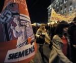 Un grupo de manifestantes pasa junto a un cartel crítico con una publicación alemana antigriega. Foto: Aris Messinis/AFP