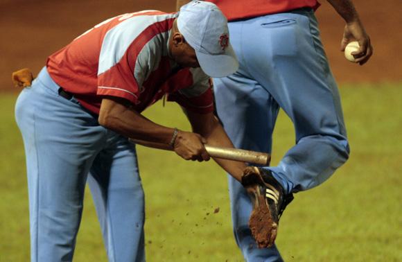 El lanzador necesita de la ayuda del carbates para quitarse el fango de los spikes.  Foto: Ismael Francisco/Cubadebate.