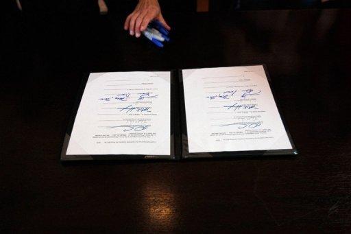 El texto de la ley que prohibe usar dinero de los contribuyentes del estado de Florida para negocios con Cuba y Siria en la mesa del gobernador Rick Scott quien lo firmó el 1 de mayo pero, de momento, no tendrá efecto pues requiere la aprobación de Washington. Foto: AFP