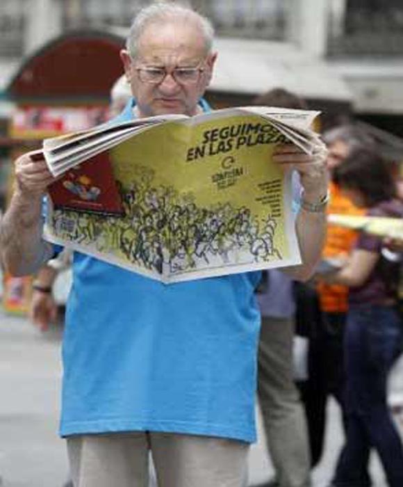 """Un """"veterano"""" indignado lee un periódico del movimiento"""