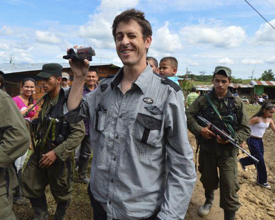 El periodista francés Romeo Langlois toma vídeo mientras es entregado por las FARC en Colombia. / LUIS ACOSTA (AFP)