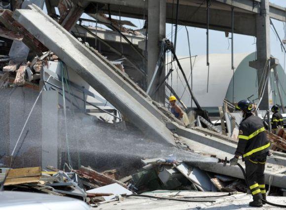 Un bombero italiano rocía agua sobre los desechos de una fábrica