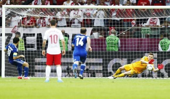 El jugador griego Giorgos Karagounis (i) lanza un penalti que detiene el portero polaco Przemyslaw Tyton (d) durante su partido del grupo A de la Eurocopa 2012 entre las selecciones de Grecia y Polonia, hoy viernes 8 de junio en el Estadio Nacional de Varsovia, Polonia. EFE/LESZEK SZYMANSKI