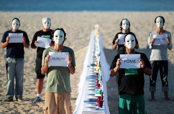 Voluntarios con máscaras realizan protesta en contra del hambre. Foto: Ueslei Marcelino/Reuters