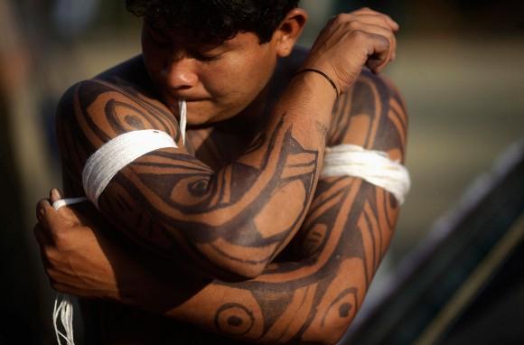 Indígena se viste para realizar ceremonia. Foto: Ricaro Moraes/Reuters