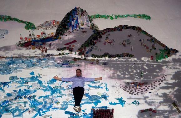 """El artista Vik Muniz posa en su obra """"Paisaje"""" en la que recrea la Bahía de Guanabara con materiales desechados. Foto: Silvia Izquierdo/AP"""