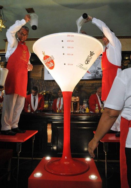 Subidos en sillas a ambos lados de la enorme copa de capitel triangular, típica del daiquiri, dos empleados fueron vertiendo las jarras. Foto: EFE/ Stringer