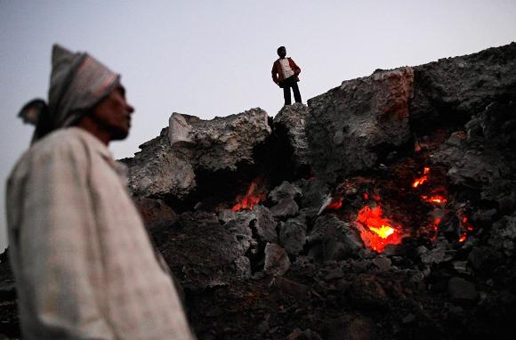 Hombres de pie junto a las brasas de un fuego subterráneo de carbón en el pueblo de Bokapahari, en el estado oriental indio de Jharkhand, donde viven y trabajan una comunidad de recolectores de carbón. Foto tomada el 6 de enero de 2011. (AP Photo / Kevin Frayer)