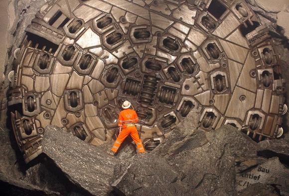 Un minero se encuentra delante de una máquina de taladro gigante después de que se rompió en la última sección de Sedrun-Faido, en el sitio de construcción del túnel de base San Gotardo NEAT 23 de marzo 2011. El proyecto consta de dos túneles paralelos de vía única, cada uno de una longitud de 57 km (35 millas). (Reuters / Arnd Wiegmann)