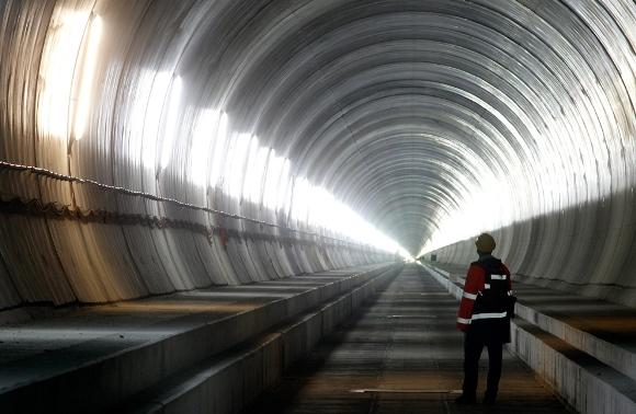 Un visitante se encuentra en la sección de Erstfeld, Amsteg de la NEAT, base del túnel de San Gotardo, octubre 5, 2010. Con una longitud de 57 km (35 millas) al cruce de los Alpes, el túnel ferrovario más largo del mundo debe estar operando a finales de 2017. (Reuters / Arnd Wiegmann)