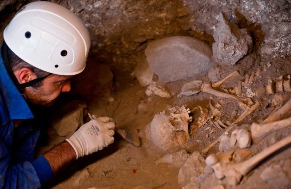 Un arqueólogo limpia un esqueleto que data de hace unos 5.000 años durante las excavaciones en los yacimientos de la sierra de Atapuerca en Burgos, norte de España, el 25 de junio de 2010. El esqueleto pertenecía a una mujer joven enterrada en la cueva de El Mirador en la Edad de Bronce. (Reuters / Félix Ordoñez)