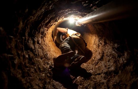 Un minero ilegal utiliza una polea rudimentaria para descender en un agujero excavado en busca de oro en un campamento improvisado por los mineros de la zona de El Callao, en el sureño estado Bolívar de Venezuela, el 15 de julio de 2010. Siete personas murieron en un derrumbe en la mina de oro salvaje en el sur de Venezuela, un importante miembro de los servicios locales de emergencia, dijo a Reuters el 24 de agosto. (Reuters / Carlos García Rawlins)
