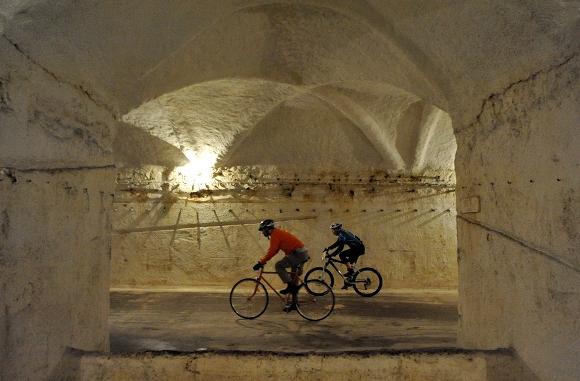 """Los participantes de la carrera de bicicletas compiten durante la """"Carrera de Mole"""" en una mina en Budapest, Hungría, el domingo, 6 de febrero 2011. Cientos participaron en la carrera, pedaleando en el medidor de 0.75 millas de largo. El sistema de minas, con más de 30 kilómetros (18.6 millas) de largo, fue utilizado durante siglos para extraer piedras para construir la capital húngara. (Foto AP / Bela Szandelszky)"""
