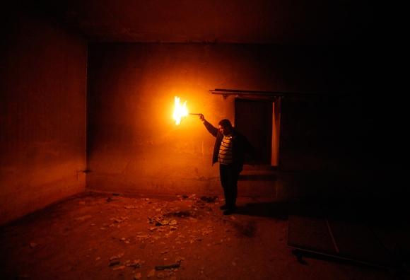 Un hombre enciende un fuego para mirar las prisiones subterráneas que formaban parte de la sede de las fuerzas leales al líder libio Muammar Gadafi en Bengasi, el 04 de marzo 2011. (Reuters/Suhaib Salem)