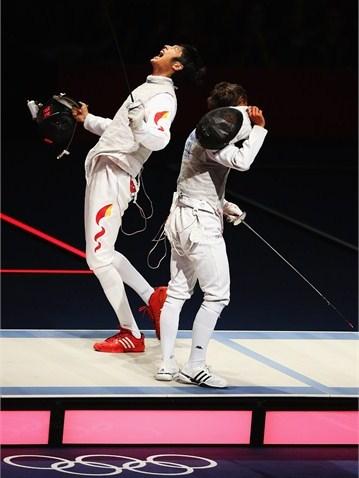 Li Sheng de China celebra su victoria ante el italiano Andrea Baldini que le concedió la Medalla de Oro del florete masculino