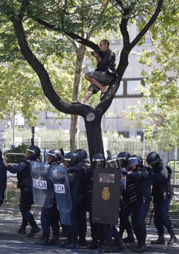 Un fotógrafo encaramado a uno de los árboles de la Castellana y rodeado de agentes antidisturbios. Foto: El País