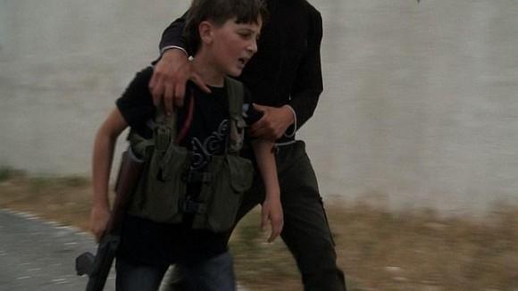 Un niño soldado es consolado por un adulto rebelde en Siria. (AFP)