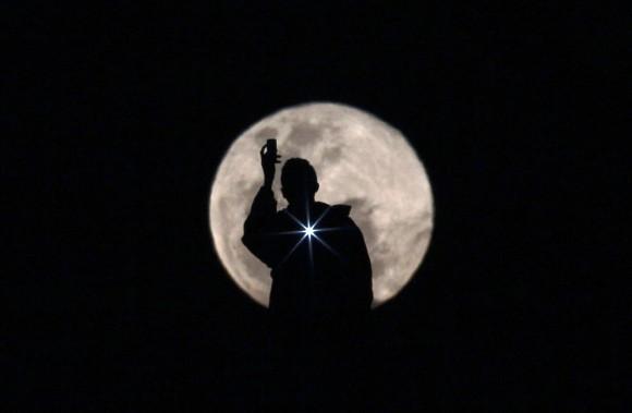 Un hombre fotografía la luna llena, en Brasilia, Brasil, el 3 de julio de 2012. Foto: Reuters / Ueslei Marcelino.