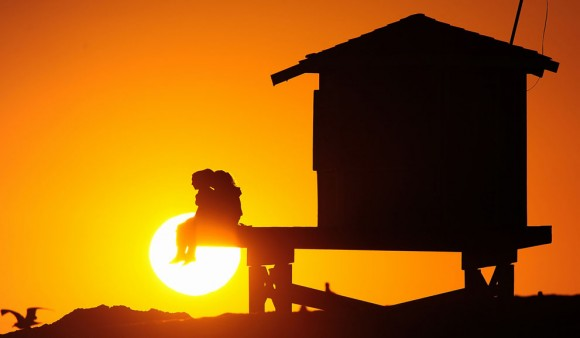 La gente disfruta de la vista, desde una estructura de socorrista, como el sol se pone en Seal Beach, al sur de Los Ángeles, California, el 9 de julio de 2012. Foto: Frederic J. Brown/AFP/Getty Images.