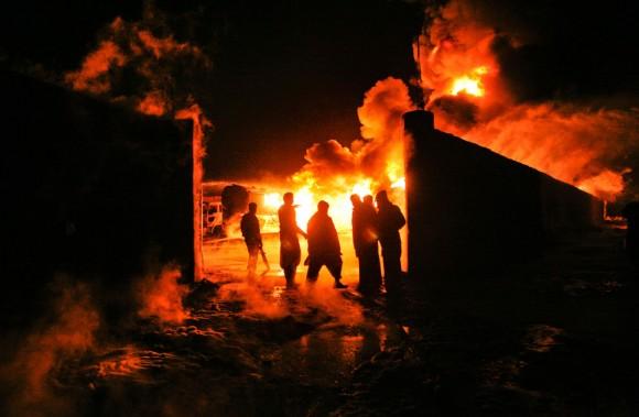 El humo se eleva cerca de los funcionarios de seguridad de pie alrededor de los camiones de combustible, que fueron incendiados en las afueras de Quetta, Pakistán, 8 de diciembre de 2011. Militantes dispararon una granada propulsada por cohete contra camiones cargados de combustible y suministros para las tropas de la OTAN en Afganistán en la ciudad suroccidental de Quetta, prendiendo fuego a 25 vehículos, dijo la policía. Foto: Reuters/Naseer Ahmed.
