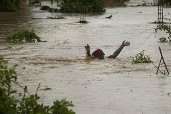 Una mujer pasa una calle inundada en Puerto Príncipe. Foto: AFP