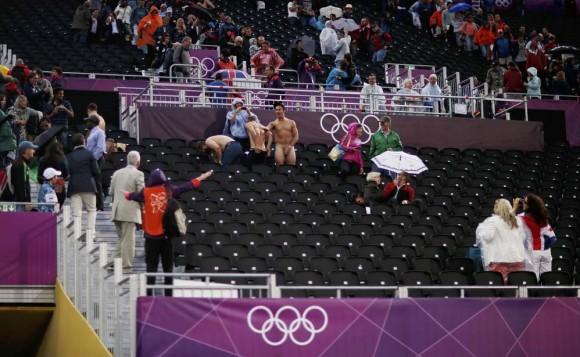 Hay gente que gusta del exhibicionismo y en esta foto vemos a un aficionado desnudo que hace gestos a un miembro del personal oficial de los Juegos Olímpicos. Esto sucedió durante el encuentro de cuartos de final del Voleibol de Playa entre Julius Brink y Jonas Reckerman de Alemanía y Ricardo y Pedro de Brasil. Foto: Reuters